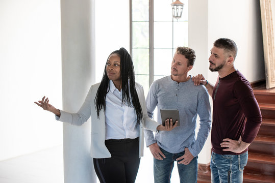 Gay couple with African American female real estate agent in new house