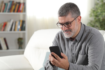 Adult man using a smart phone at home