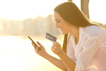 Happy woman pays online with credit card at sunset