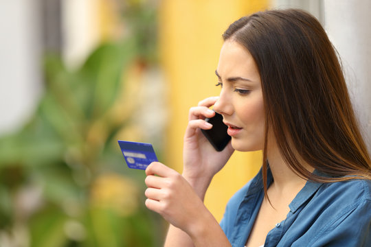 Serious online buyer talking on phone holding credit card