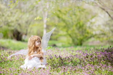 Fairy tale consept. Little girl wearing beautiful princess dress with fairy wings, spring day