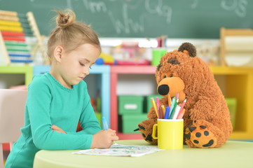 Portrait of cute little girl drawing in her room