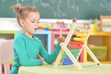 Portrait of little girl sitting and counting on abacus