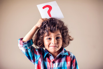 Kid boy with question mark. Children, education and emotions concept