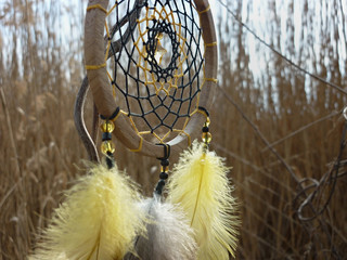Dream catcher with yellow feathers on the background of reeds. Dreamcatcher sunset, mountains, boho-chic, ethnic amulet, symbol.