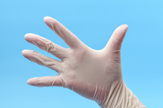 Hand Wearing Protective or Surgical Gloves on a Blue Background. Hand in white medical gloves , in position open palm. Medical background.
