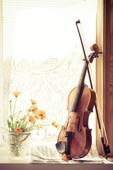 Vertical image of flowers and violin with sheet music  the front of the fiddle on windows background.
