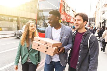 Happy friends with takeaway pizza in London