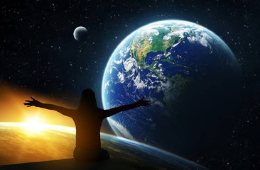 Back view of woman with hands up looking at planets,  Borderless communication conceptElements of this image are furnished by NASA.