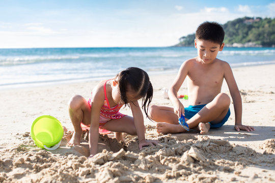 Two children playing with sand on beach
