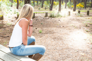 back view of blonde pretty young woman on a summer day girl sit on wood bench table