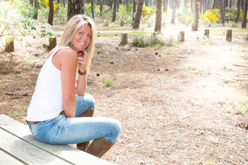 Relaxed happy blonde woman outdoor park sit on wood bench table