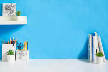 office creative desk with supplies, and blue wall.