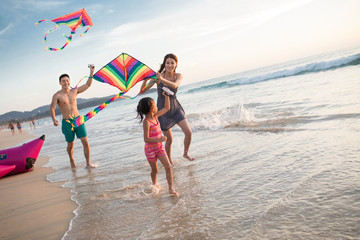Happy young family flying a kite on beach