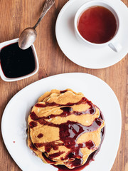 Pancakes with cherry syrup. Tea. Wooden table.