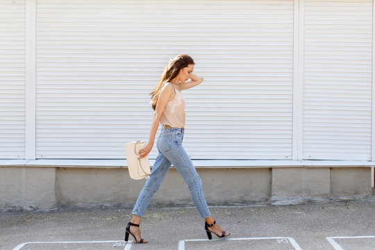 Young stylish woman wearing beige cami silk top, blue cropped denim jeans, black high heel sandals and holding clutch bag walking in the city street. Trendy casual outfit. Street fashion.