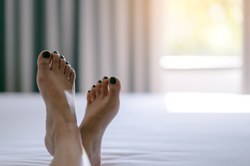Closeup image of a woman's feet on a white bed