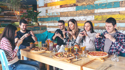 Happy friends taking pictures of pizza and hamburgers with mobile phones to post online