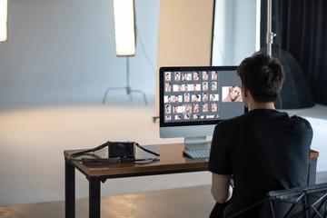 Young photographer retouching photos in studio