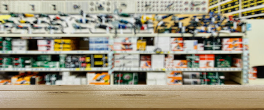 Shop for selling electric tools. Drills, screwdrivers, electric saws, grinder. Defocused, blurred image. In the foreground is the top of a wooden table, counter.