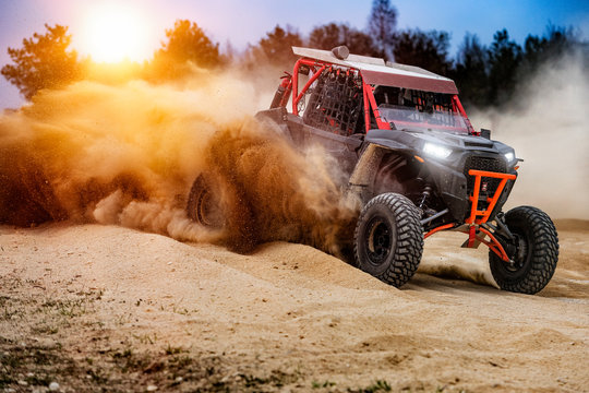 UTV buggy in the action on sand with sunshine