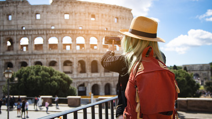 Back view of young woman with hat she's take a picture by smartphone at Colosseum in Rome, Italy. Rome architecture and landmark