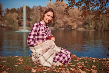 Cute woman with a blanket by the lake in autumn park
