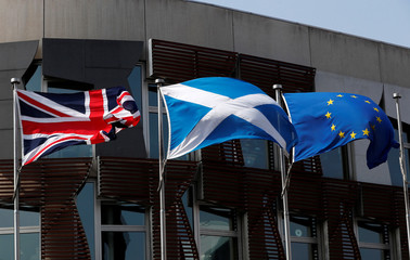 A Scottish flag flies between British Union Jack flag and European Union flag outside the Scottish Parliament in Edinburgh