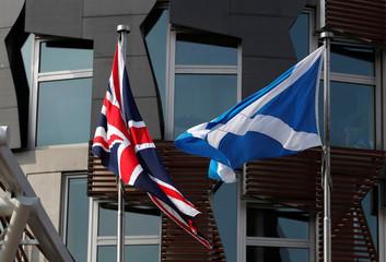 A Scottishflag flies next to BritishUnionJackflag outside the Scottish Parliament in Edinburgh