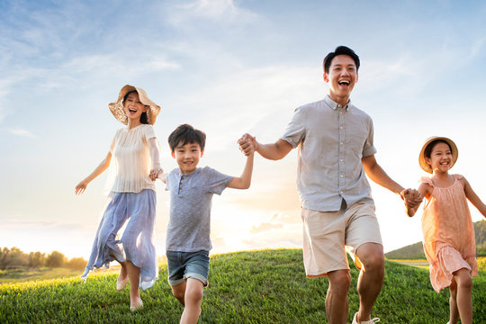 Happy young family running on meadow