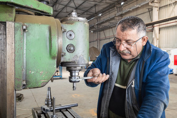 Blue-collar worker using milling machine in workshop