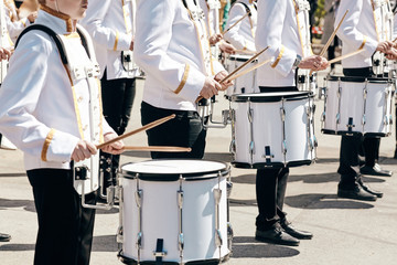 The ensemble of drummers in white ceremonial dress, performing in the spring in the city park.