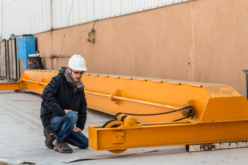 Young engineer controlling the bridge crane in the factory