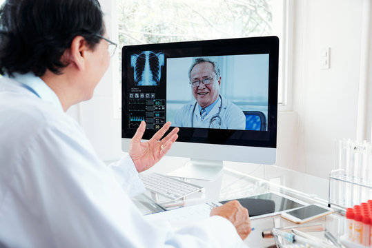 Doctor consulting coworker via video conference
