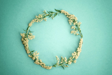 Floral round frame made of yellow flowers on light paper green background image Black and white photo