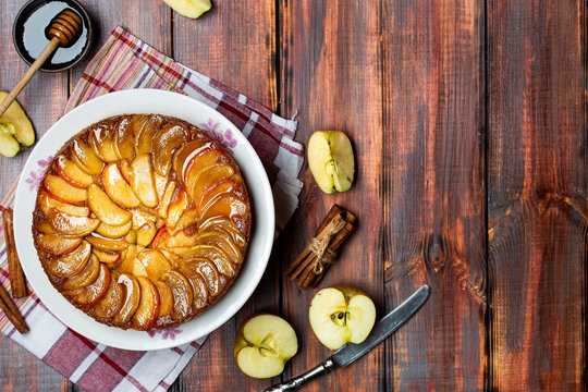 apple tart with caramel and cinnamon on wooden table