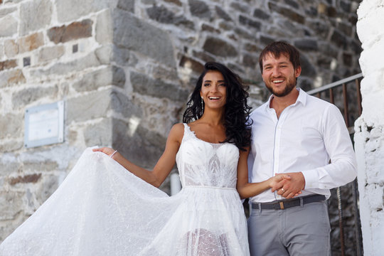 Happy portrait of a couple newlyweds poses embracing together near old grey wall in greece. Important celebration. copy space.