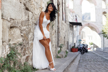 Image of a gorgeous brunette bride poses sensual near old town in greece, summer time. Wedding in Greece.