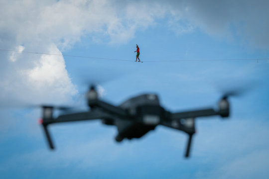 a drone filming a man walking on the longest slackline ever in Navacelles circus (world humanity patrimony) at 300 meters high, Occitanie, Navacelles, France