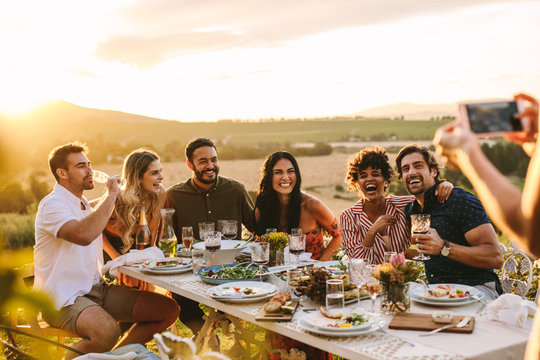 Woman taking picture of her friends at dinner party