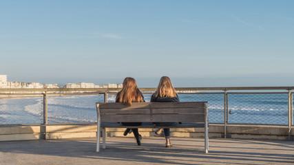 Deux femmes regardant l'océan assises sur un banc en fin d'après midi