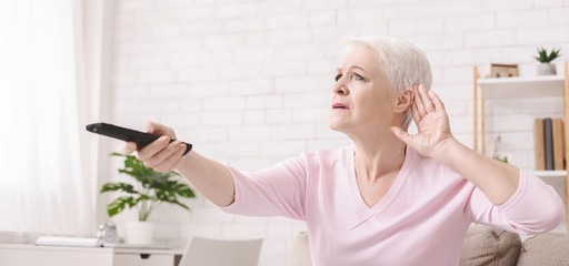 Elderly woman rising tv set volume with remote control