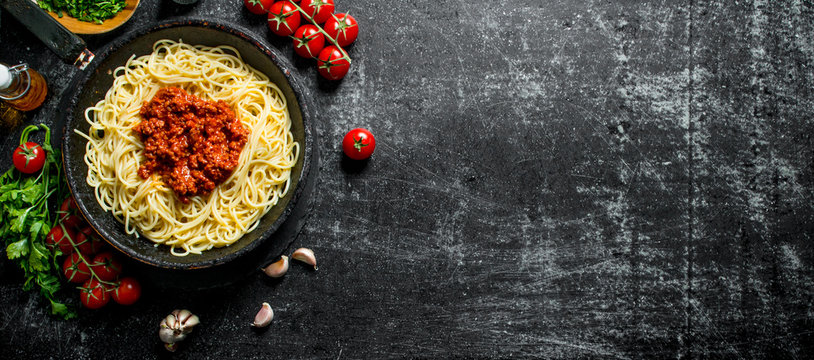 Spaghetti with Bolognese sauce in pan with tomatoes, herbs and garlic.