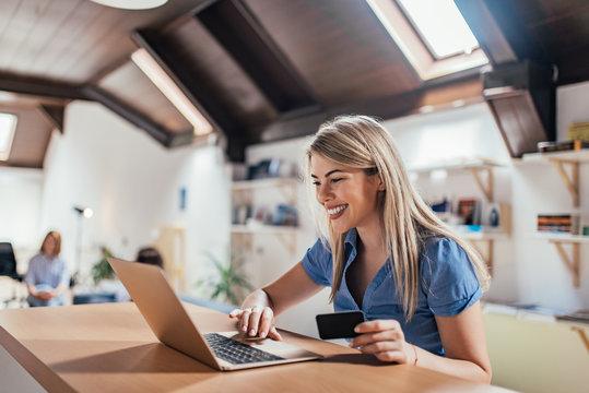 Happy young woman doing e-shopping.