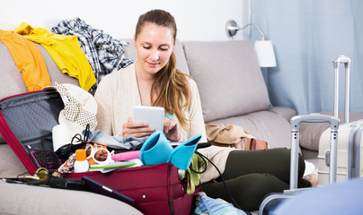 Young female choosing resort or ticket online