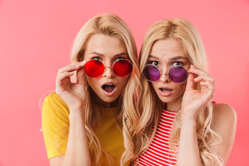 Shocked blonde twins holding their sunglasses and looking at camera Wall mural