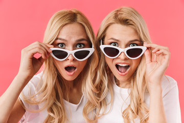 Shocked blonde twins take off sunglasses and looking at camera Wall mural