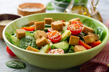 Vegan salad with spinach, cucumber, tomatoes, avocado, fried tofu and sesame. Selective focus.