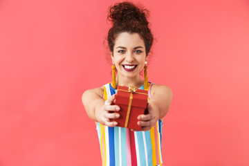 Smiling pretty redhead woman in dress giving gift box