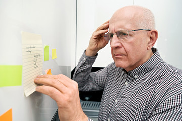 Elderly man with dementia looking at notes Wall mural